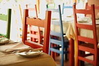 Different colored chairs at tables set for dining in Lisbon, Portugal