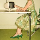 Side view of Caucasian mid_adult woman wearing green vintage dress sitting at 50's retro dinette set turning old televsion knob