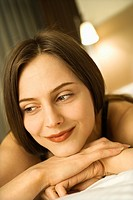 Portrait of Caucasian mid_adult woman smiling with head resting on hands