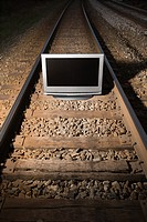 Flat panel television set on railroad tracks at night