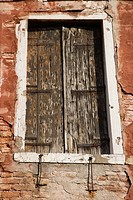 Worn building with window with closed wooden shutters in Venice, Italy