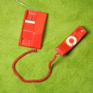Red vintage rotary telephone on 70's green carpet
