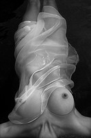 Young nude Asian woman floating in water with with sheer fabric wrap