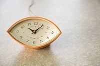 Still life of orange eye-shaped vintage clock on table (thumbnail)