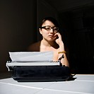 Nude young Asian woman sitting at kitchen table with typewriter