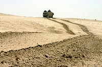 Amphibious assault vehicle rolls through a desert field