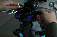 Airman adjusts the eyespan on night vision goggles