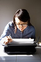 Pretty young Asian woman sitting in chair typing on typewriter in kitchen