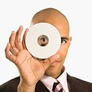 African American man holding compact disc over face and peeking through hole