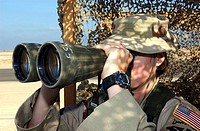 Airman uses binoculars to watch avenues of approach