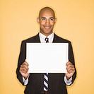 African American man smiling holding blank sign against yellow background
