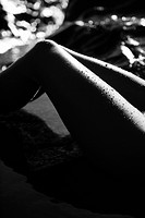 Filipino young woman's legs in water on rocky beach