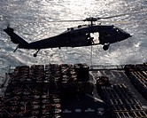 An MH_60S Seahawk helicopter conducts a vertical replenishment