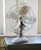 Retro style metal fan sitting on tabletop by window