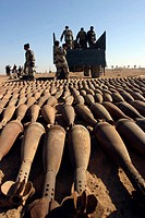 Soldiers load hundreds of 120 millimeter white phosphorous mortar rounds onto a truck