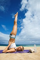 Caucasian young adult woman doing yoga on beach (thumbnail)