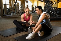 Prime adult Caucasian female with personal trainer at gym