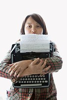 Pretty young Asian woman holding typewriter