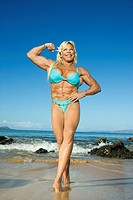 Pretty Caucasian mid adult woman bodybuilder in bikini flexing bicep on beach