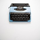 Blue vintage typewriter on white background