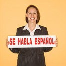 Caucasian businesswoman smiling holding sign reading 'se habla espanol.'
