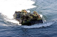 An amphibious assault vehicle drives toward a ship
