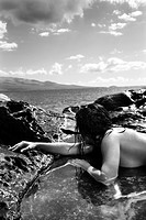 Close up of nude Caucasian mid adult woman lying in tidal pool at coast looking toward ocean (thumbnail)
