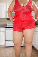 Full figured Caucasian young woman in sexy red lingerie standing in kitchen
