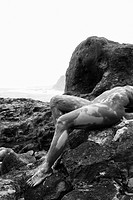 Young adult Caucasian female nude lying on rock 