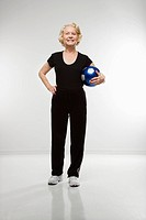 Caucasian senior woman standing holding soccer ball