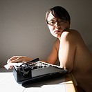 Pretty nude young Asian woman sitting at kitchen table with typewriter