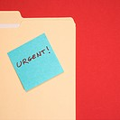 Folder with a blue sticky note attached reading urgent on a red background