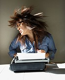 Pretty young Asian woman sitting at typewriter swinging head and hair around