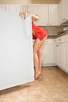 Caucasian young woman in sexy red lingerie looking in refrigerator