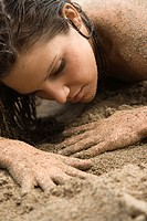 Head shot of Caucasian young adult nude woman lying in sand