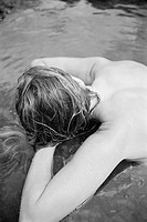 Above view of sexy partially nude Caucasian woman lying in tidal pool 