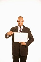 African American man holding and pointing to blank sign standing against white background