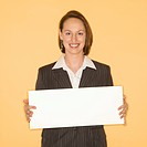 Caucasian businesswoman smiling holding blank sign