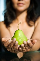 Woman holding pear in outstretched hands toward viewer.
