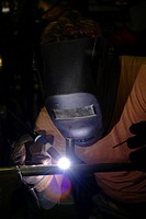 U.S. Navy Hull Maintenance Technician welds a fitting to a pipe