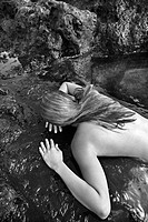 Young nude Asian woman lying face down on rocks