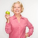 Caucasian senior woman holding apple smiling at viewer
