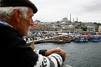 Fishermen standing on the Galata bridge with a view over the Bazaar Quarter, Istanbul, Turkey