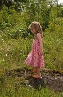 Young girl walking on a rock