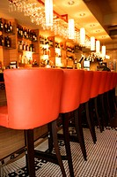 Bar stools in a row in front of bar counter with modern style