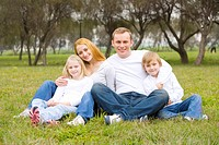 Family sitting on grass, smiling, portrait