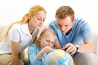Parents and daughter looking at the globe, concentrating