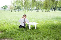 One mid adult man drinking coffee with laptop on desk outdoors