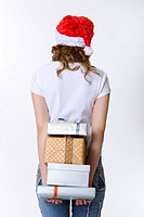 Teenage girl wearing Santa hat holding stack of gifts behind back, rear view