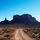 Dirt road headed toward rock formations in desert of Monument Valley, Utah